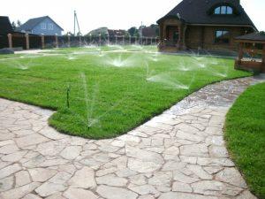 Автоматический полив газона дождеванием.
